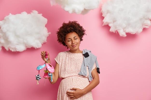 Blije donkere vrouw die haar zwangere buik streelt, voelt dat haar pasgeboren kind de ogen sluit en staat kalm geniet van zwangerschap draagt babys items poses