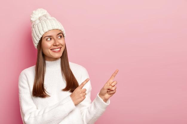 Blije donkerharige vrouw staat opzij en wijst naar lege kopie ruimte, gekleed in winter outfit, glimlacht gelukkig, geïsoleerd op roze achtergrond