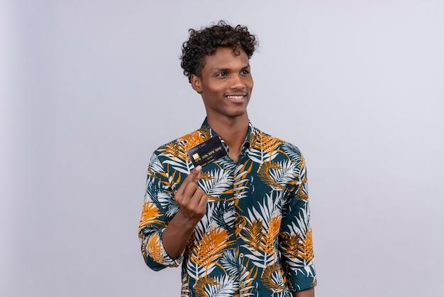 Blije en glimlachende knappe donkere man met krullend haar in bladeren bedrukt overhemd met creditcard