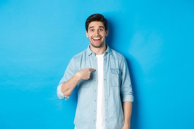 Blije en verraste man die naar zichzelf wijst, tevreden glimlacht, staande tegen een blauwe achtergrond