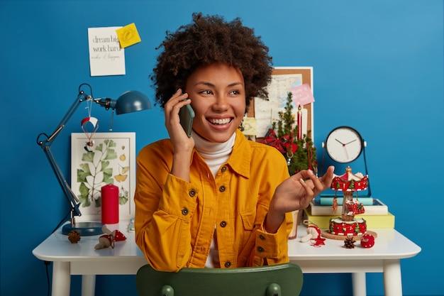 Blije etnische vrouw met knapperig haar grijnst vrolijk terwijl ze via smartphone praat, steekt handpalm op, gekleed in modieus geel jasje