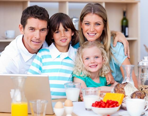 Blije familie die laptop met behulp van tijdens het ontbijt