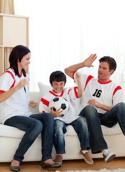 Blije familie die op voetbalwedstrijd let