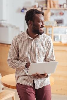 Blije freelancer. vrolijke jonge man leunend op de tafel in het koffiehuis, houdt een laptop vast en kijkt weg van de camera terwijl hij aangenaam lacht