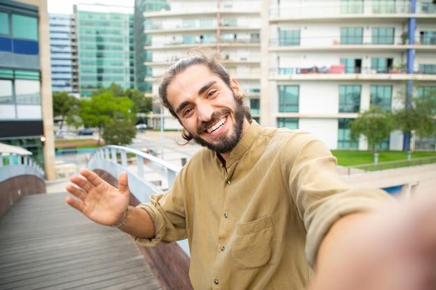 Blije gelukkige hipsterkerel die selfie nemen