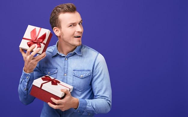 Blije gelukkige jonge man luistert wat rammelt in een cadeau.