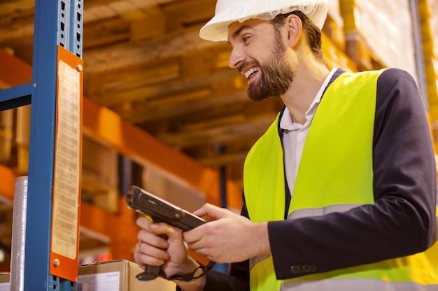Blije gelukkige man die een scanner gebruikt voor het inventariseren in het magazijn