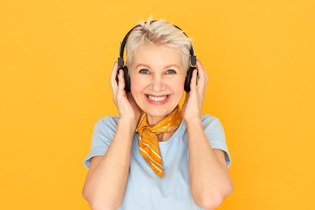 Blije gelukkige rijpe kortharige vrouw die in grote lijnen op geel in draadloze hoofdtelefoons glimlacht