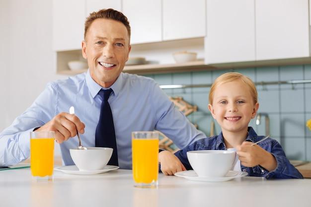 Blije gelukkige vader en dochter die aan de tafel zitten en naar je kijken terwijl ze samen ontbijten