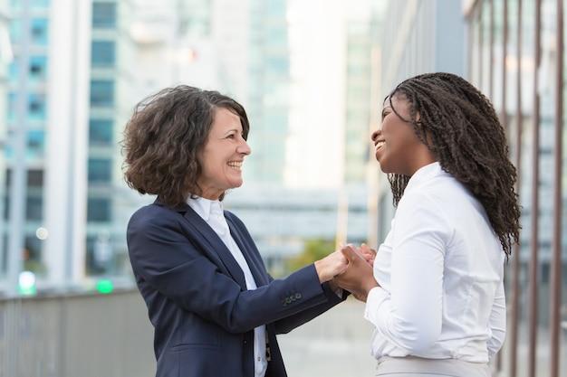 Blije gelukkige vrouwelijke collega's die goed nieuws delen
