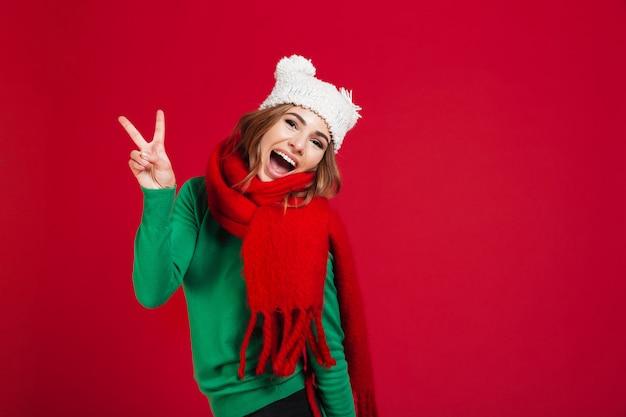 Blije gillende donkerbruine vrouw in sweater, grappige hoed en sjaal