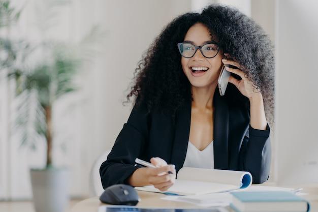Blije glimlachende donkere vrouw belt zakenpartner, in goed humeur, maakt notities, zit op de werkplek