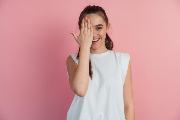 Blije, glimlachende vrouw met één oog, met de hand gesloten