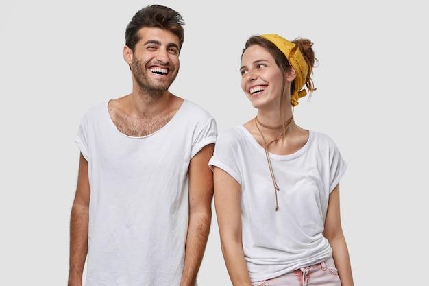 Blije groepsgenoten verheugen zich over geslaagd examen, kijken gelukkig naar elkaar, lachen om goede grap, uiten positieve emoties, geïsoleerd over witte muur