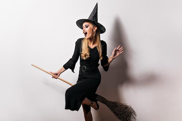 Blije heks die op bezem in halloween vliegt. indoor portret van enthousiaste vrouwelijke tovenaar in zwarte jurk.