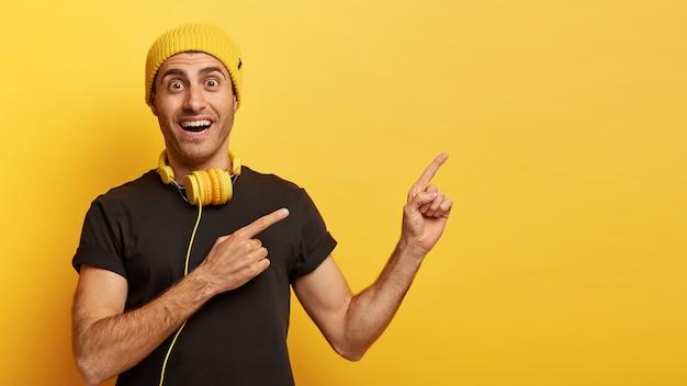 Blije hipster-man wijst met beide wijsvingers opzij, adverteert kopie ruimte voor uw advertentie-inhoud
