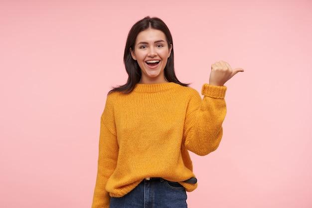 Blije jonge aantrekkelijke langharige donkerbruine vrouw met natuurlijke make-up die opzij duimen en gelukkig lacht terwijl zij zich over roze muur in vrijetijdskleding bevindt