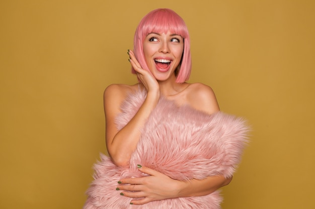 Blije jonge aantrekkelijke roze harige vrouw met groene manicure die vrolijk opzij kijkt en haar mond wijd open houdt, pluizig kussen over mosterdmuur houdt