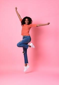 Blije jonge afrikaanse vrouw in oranje en overhemd die geïsoleerd over over roze studioachtergrond springen vieren.