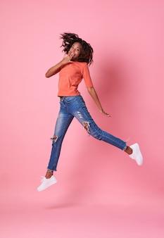 Blije jonge afrikaanse vrouw in oranje overhemd die en over roze achtergrond springen vieren.