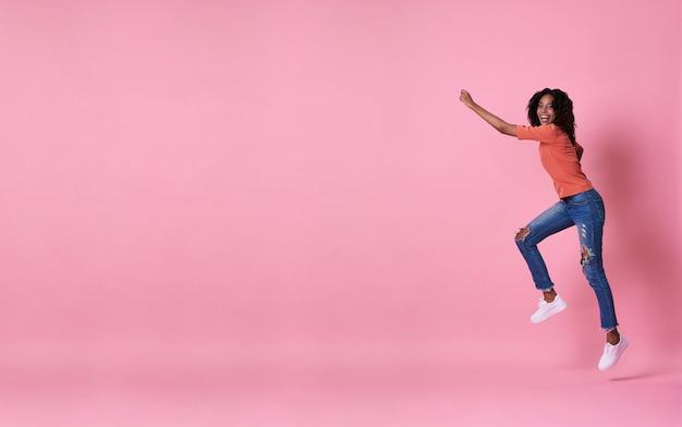 Blije jonge afrikaanse vrouw in oranje overhemd die en over roze met exemplaarruimte springen vieren.