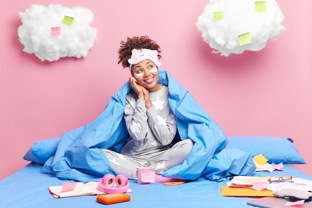 Blije jonge afro-amerikaan gekleed in nachtkleding kijkt opzij met peinzende gezichtsuitdrukking brengt schoonheidspleisters onder de ogen aan om wallen te verminderen reduce