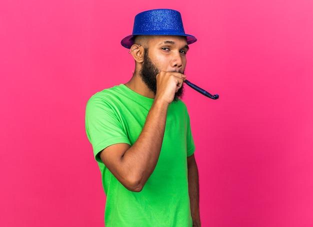 Blije jonge afro-amerikaanse man met een feestmuts die een feestfluitje blaast dat op een roze muur wordt geïsoleerd