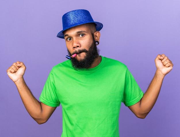 Blije jonge afro-amerikaanse man met een feestmuts die een feestfluitje opblaast met ja gebaar geïsoleerd op een blauwe muur