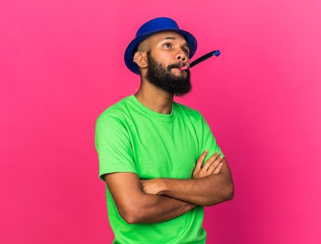Blije jonge afro-amerikaanse man met feestmuts die feestfluitje blaast en handen kruist geïsoleerd op roze muur