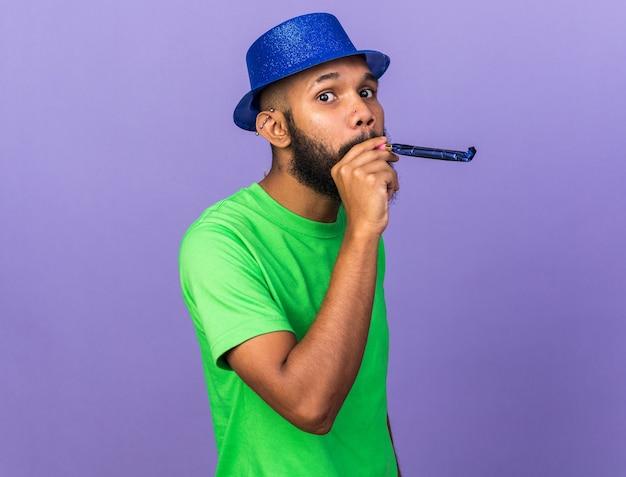 Blije jonge afro-amerikaanse man met feestmuts die feestfluitje blaast