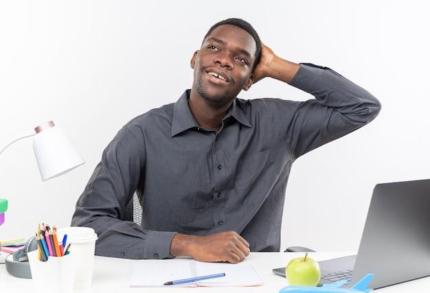 Blije jonge afro-amerikaanse student die aan een bureau zit met schoolgereedschap, hand op zijn hoofd legt en naar de zijkant kijkt
