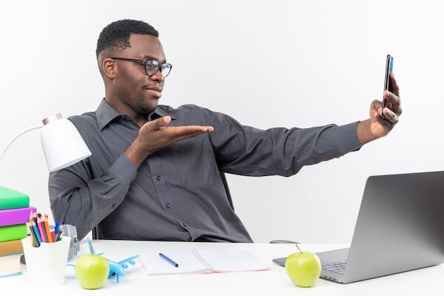 Blije jonge afro-amerikaanse student in optische bril zit aan bureau met schoolhulpmiddelen op zoek
