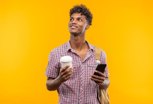 Blije jonge afro-amerikaanse student met rugzak met telefoon en papieren beker die naar de zijkant kijkt