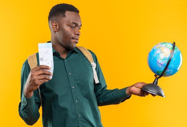 Blije jonge afro-amerikaanse student met rugzak met vliegticket en kijkend naar globe geïsoleerd op oranje muur met kopieerruimte