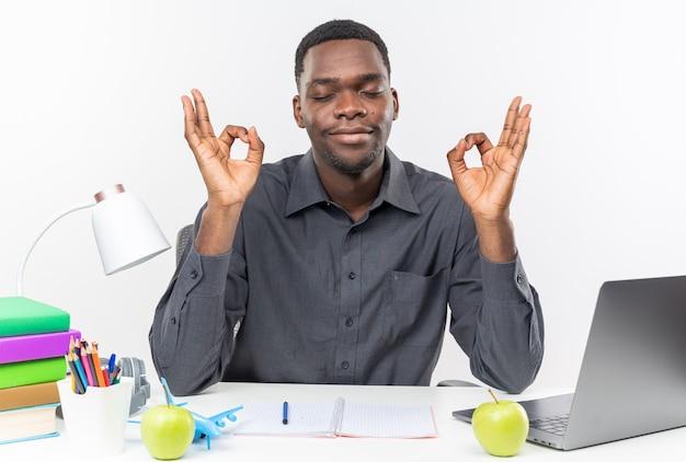 Blije jonge afro-amerikaanse student zit met gesloten ogen aan bureau met schoolhulpmiddelen mediteren geïsoleerd op een witte muur