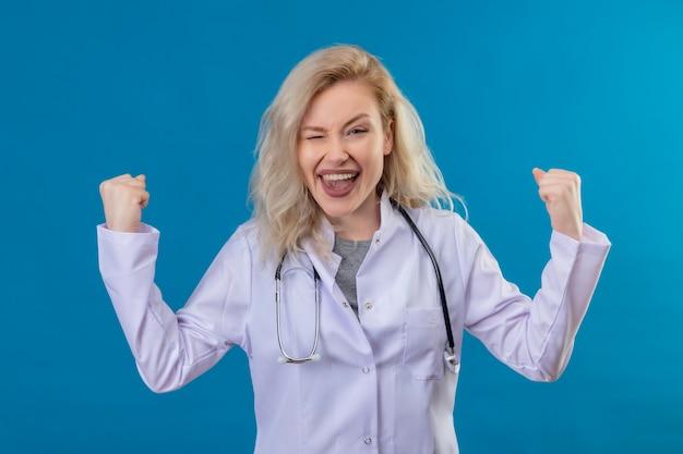 Blije jonge arts die stethoscoop in medische toga draagt die sterk gebaar op blauwe muur doet