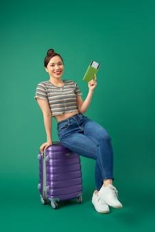 Blije jonge aziatische meisjeszitting op koffer en houdt paspoort, vliegticket om over groen te reizen.