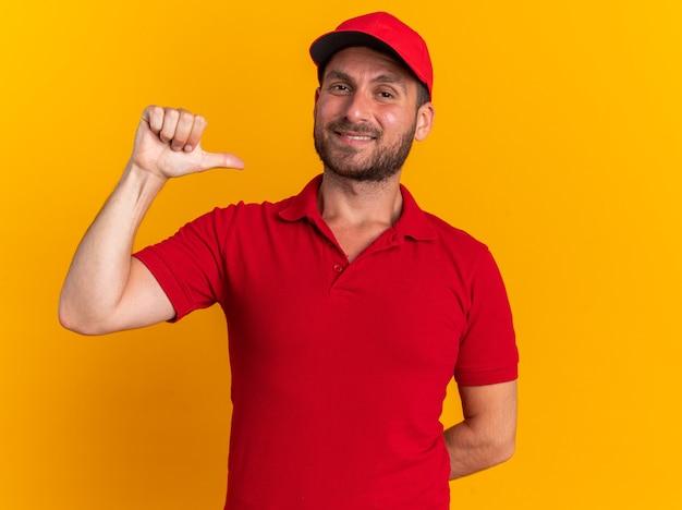 Blije jonge blanke bezorger in rood uniform en pet met hand achter de rug kijkend naar camera wijzend op zichzelf geïsoleerd op oranje muur