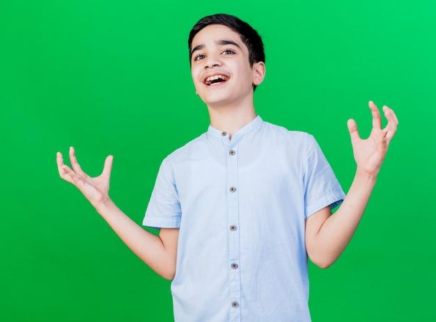 Blije jonge blanke jongen die lege handen toont die op groene muur worden geïsoleerd