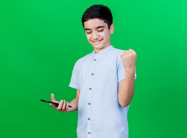 Blije jonge blanke jongen die mobiele telefoon houdt die ja gebaar doet dat op groene muur met exemplaarruimte wordt geïsoleerd