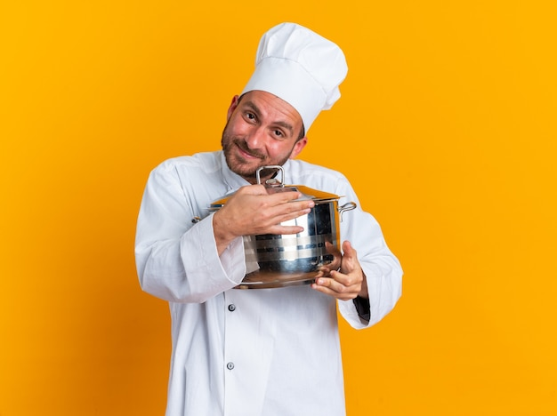 Blije jonge blanke mannelijke kok in chef-kokuniform en dop die pot vasthoudt en knuffelt