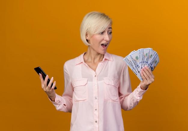 Blije jonge blonde slavische telefoon van de vrouwenholding en contant geld in haar hand kijken