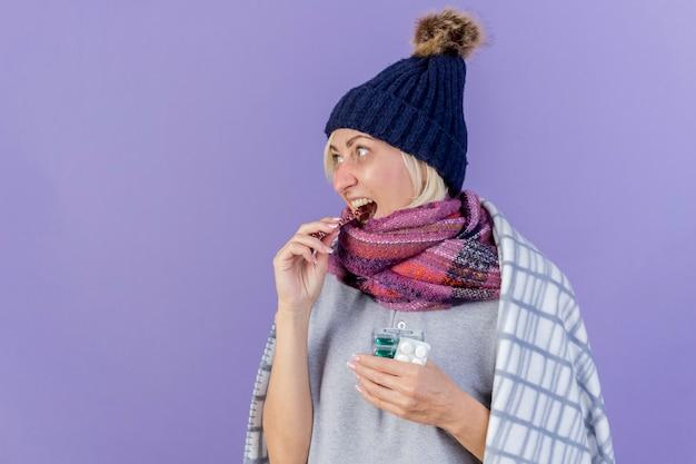 Blije jonge blonde zieke slavische vrouw die de winterhoed en sjaal draagt
