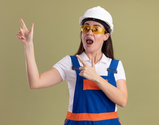 Blije jonge bouwersvrouw in eenvormig en glazen wijst aan kant die op olijfgroene muur met exemplaarruimte wordt geïsoleerd