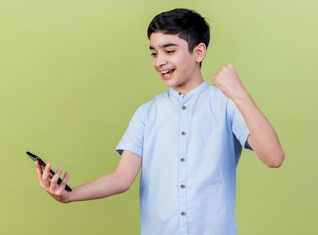 Blije jonge jongen die en mobiele telefoon houdt bekijkt die ja gebaar doet dat op olijfgroene muur wordt geïsoleerd