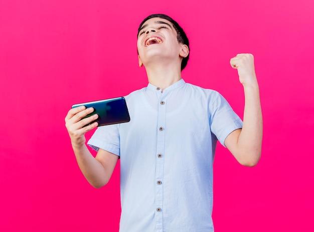 Blije jonge jongen die mobiele telefoon houdt die ja gebaar met gesloten ogen doet die op roze muur wordt geïsoleerd