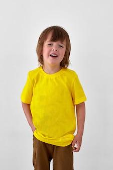 Blije jonge jongen in geel t-shirt die tegen een witte achtergrond staat en wegkijkt