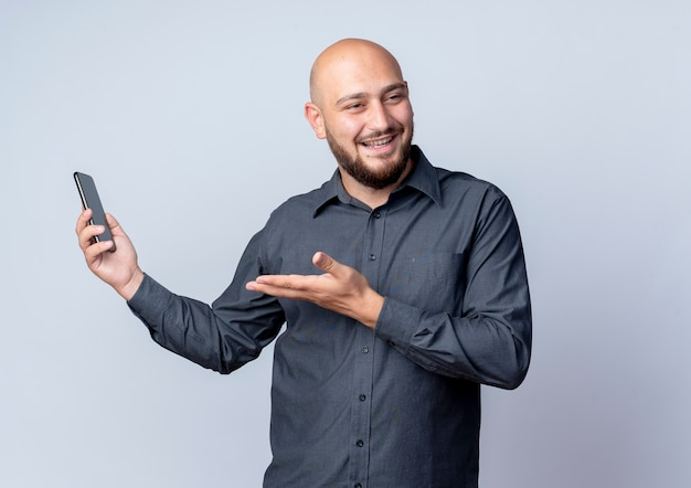 Blije jonge kale callcentermens die mobiele telefoon houdt die kant bekijkt en lege die hand toont die op wit wordt geïsoleerd