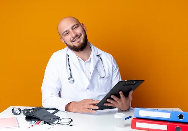 Blije jonge kale mannelijke arts met een medisch gewaad en een stethoscoop die aan het bureau zit