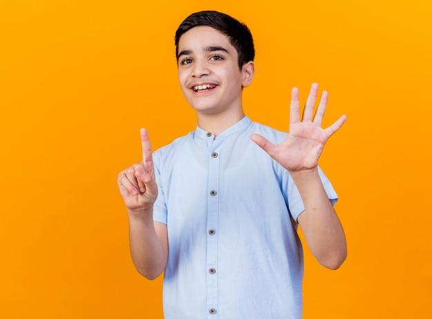 Blije jonge kaukasische jongen die camera bekijkt die zes met handen toont die op oranje achtergrond met exemplaarruimte worden geïsoleerd